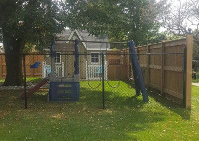Wooden and chainlink fence around children's yard
